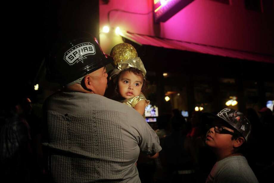 Andy Macias of San Antonio holds his daughter, Karina, 2, dressed as a trophy during the NBA Finals in downtown San Antonio on Tuesday, June 18, 2013. His older daughter wore the outfit when the Spurs were in the championship in 2007. Photo: Abbey Oldham, San Antonio Express-News / © San Antonio Express-News