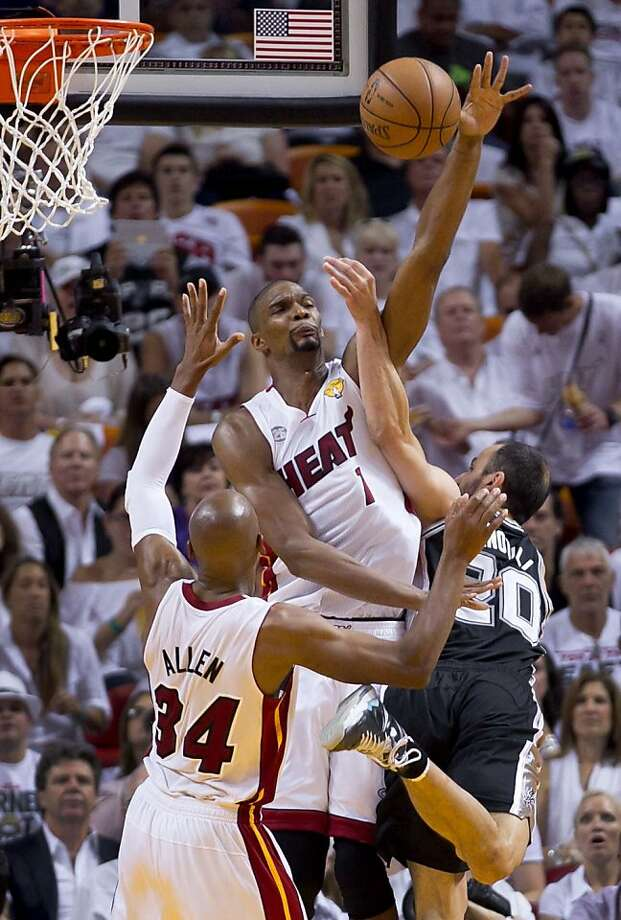 Chris Bosh blocks Manu Ginobili's shot. Bosh finished with 10 points, 11 rebounds and two crucial late-game blocks. Photo: Allen Eyestone, McClatchy-Tribune News Service