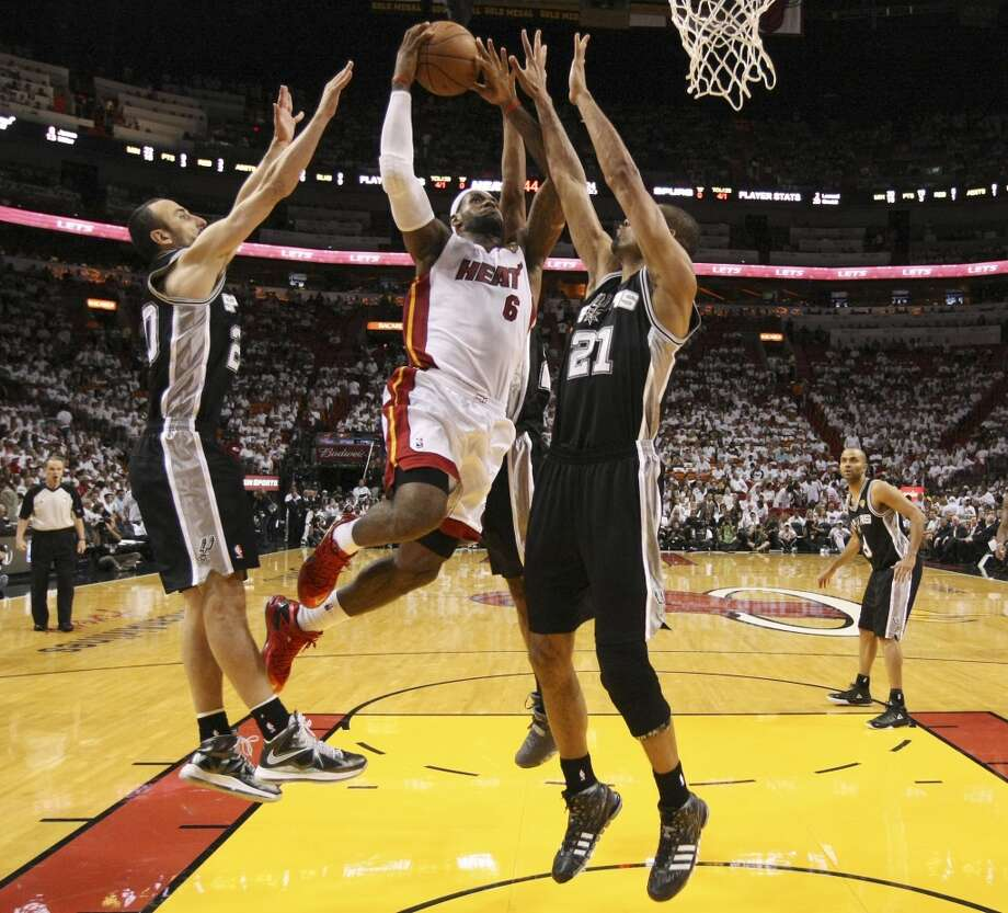 Miami Heat's LeBron James goes up for a shot in between San Antonio Spurs' Manu Ginobili and Tim Duncan during Game 6 of the NBA Finals at American Airlines Arena on Tuesday, June 18, 2013 in Miami. (Kin Man Hui/San Antonio Express-News)