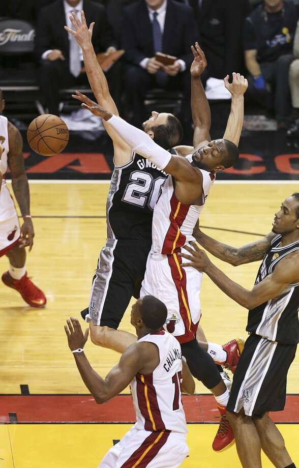 San Antonio Spurs' Manu Ginobili  is striped of the ball by Miami Heat's Dwyane Wade and other Heat players late in overtime of Game 6 of the NBA Finals at American Airlines Arena on Tuesday, June 18, 2013 in Miami. (Jerry Lara/San Antonio Express-News)