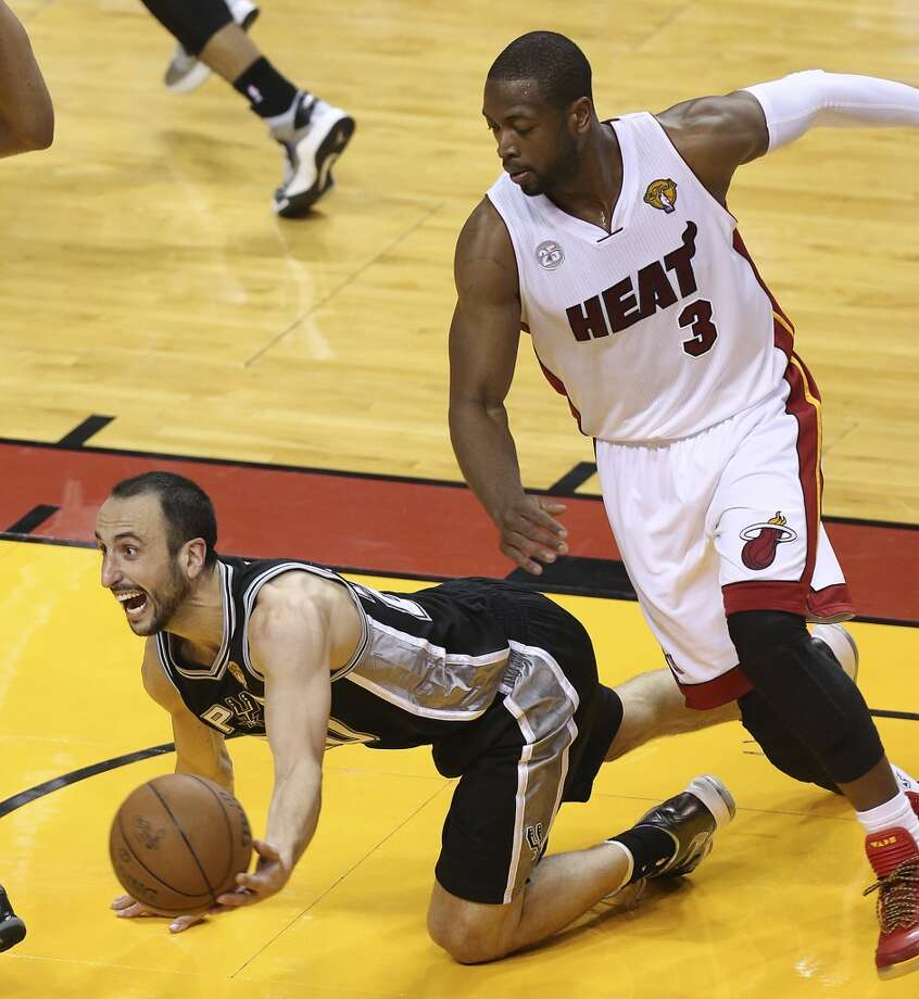San Antonio Spurs' Manu Ginobili pass a rebound as Miami Heat's Dwyane Wade put pressure during overtime of Game 6 of the NBA Finals at American Airlines Arena on Tuesday, June 18, 2013 in Miami. (Jerry Lara/San Antonio Express-News)
