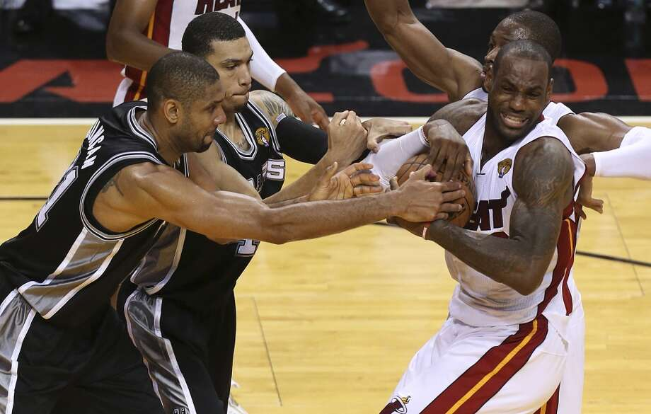 Miami Heat's LeBron James gets a rebound under pressure from San Antonio Spurs' Tim Duncan and Danny Green during overtime of Game 6 of the NBA Finals at American Airlines Arena on Tuesday, June 18, 2013 in Miami. (Jerry Lara/San Antonio Express-News)