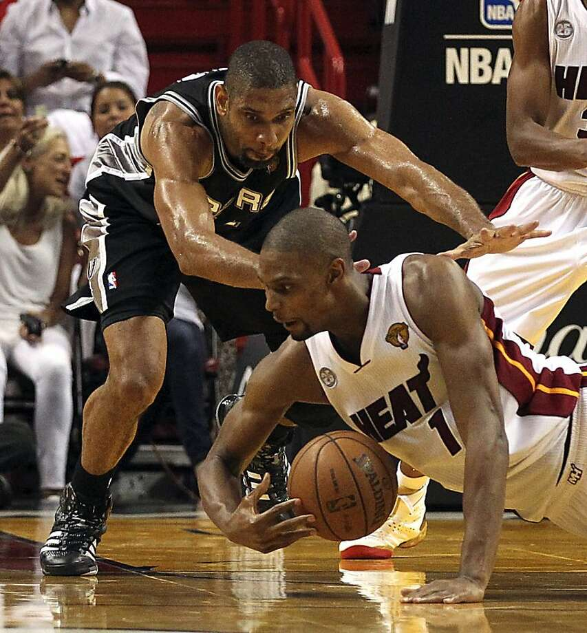 The Miami Heat's Chris Bosh grabs a loose ball from the San Antonio Spurs' Tim Duncan in the second quarter in Game 6 of the NBA Finals on Tuesday, June 18, 2013, at the AmericanAirlines Arena in Miami, Florida. (Charles Trainor Jr./Miami Herald/MCT) Photo: Charles Trainor Jr, McClatchy-Tribune News Service