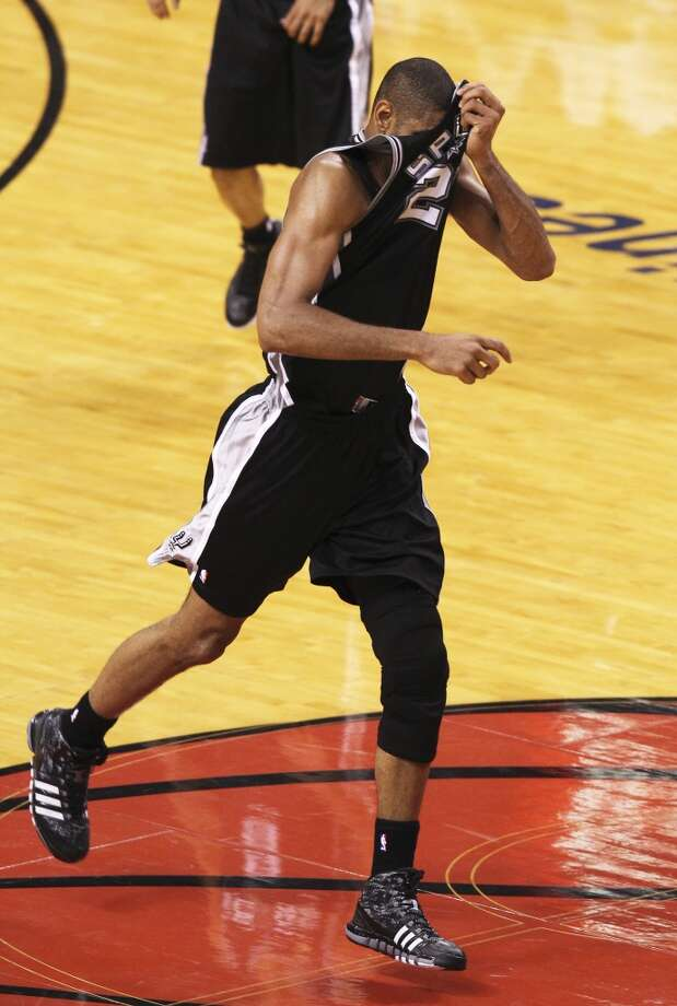 San Antonio Spurs' Tim Duncan pulls up his jersey to wipe his face during the first half of Game 6 of the NBA Finals at American Airlines Arena on Tuesday, June 18, 2013 in Miami. (Kin Man Hui/San Antonio Express-News)