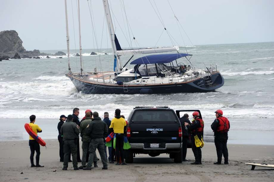 Local and state police gather on the beach as they negotiate with the 3 suspects that are still aboard the stolen yacht.  An 82 foot sailboat stolen from the Sausalito Yacht Harbor is run aground with suspects  still aboard at Linda Mar Beach in Pacifica, CA Monday March 4th, 2013.