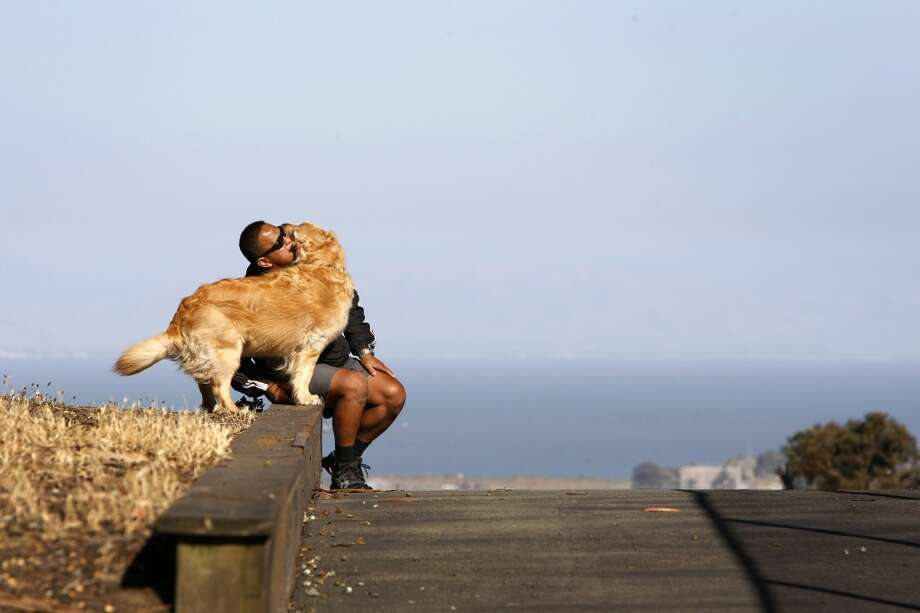 Charles Almazar plays with Lily, his golden retriever, in Holly Park on June 8, 2013 in San Francisco, Calif.