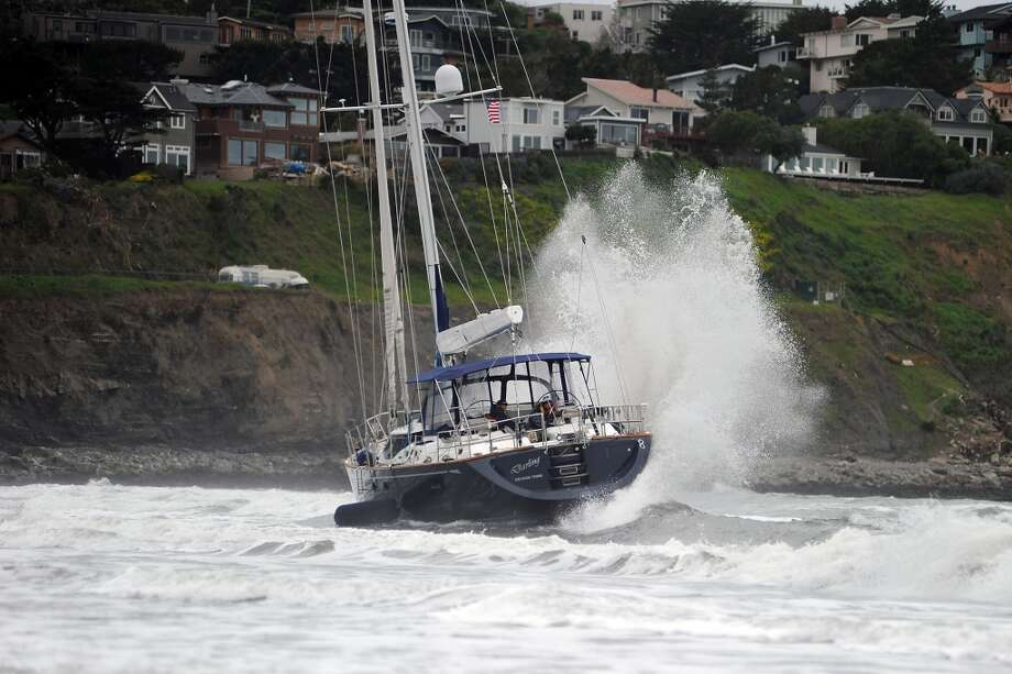 Waves batter the yacht as it sits in the surf at Linda Mar Beach.  An 82 foot sailboat stolen from the Sausalito Yacht Harbor is run aground with suspects  still aboard at Linda Mar Beach in Pacifica, CA Monday March 4th, 2013.