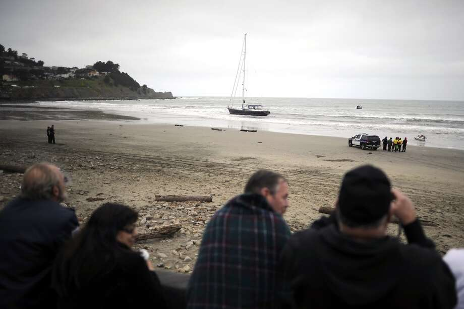 "On lookers gather at Taco Bell to watch as police negotiate with 3 suspects aboard the ""Darling"" sailboat.  An 82 foot sailboat stolen from the Sausalito Yacht Harbor is run aground with suspects  still aboard at Linda Mar Beach in Pacifica, CA Monday March 4th, 2013."