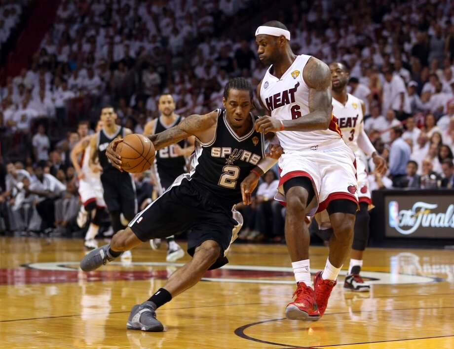 Kawhi Leonard of the Spurs drives to the basket against Heat forward LeBron James.