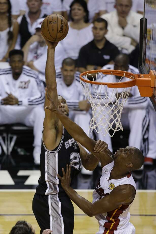 Tim Duncan of the Spurs dunks over Heat forward Chris Bosh.