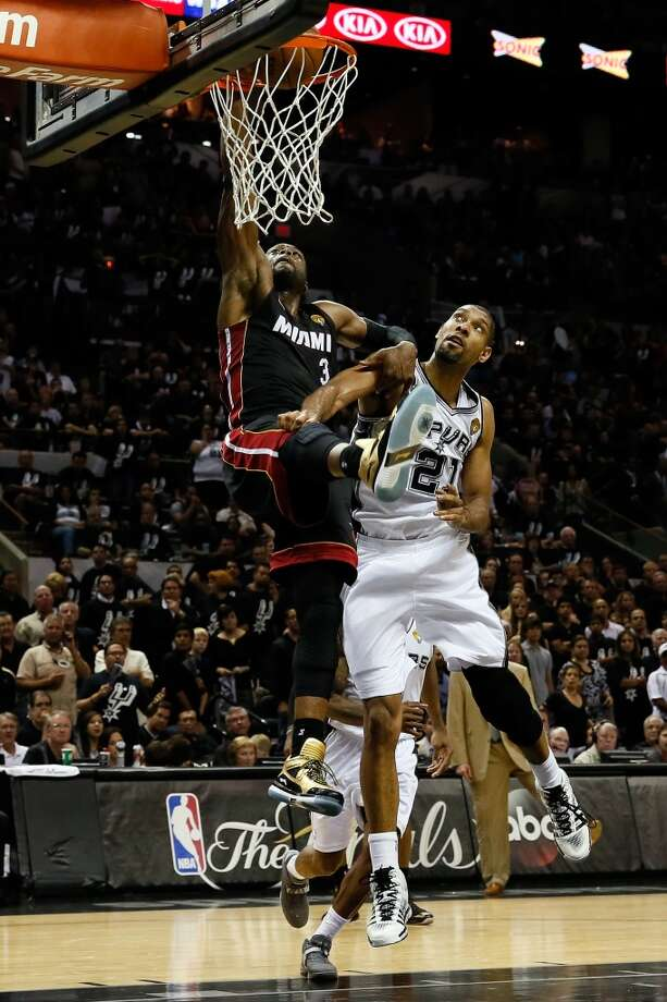 Dwyane Wade of the goes up for a dunk over Tim Duncan.