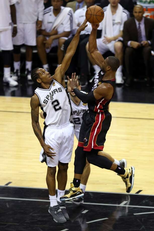 Dwyane Wade goes up for a shot over Kawhi Leonard.