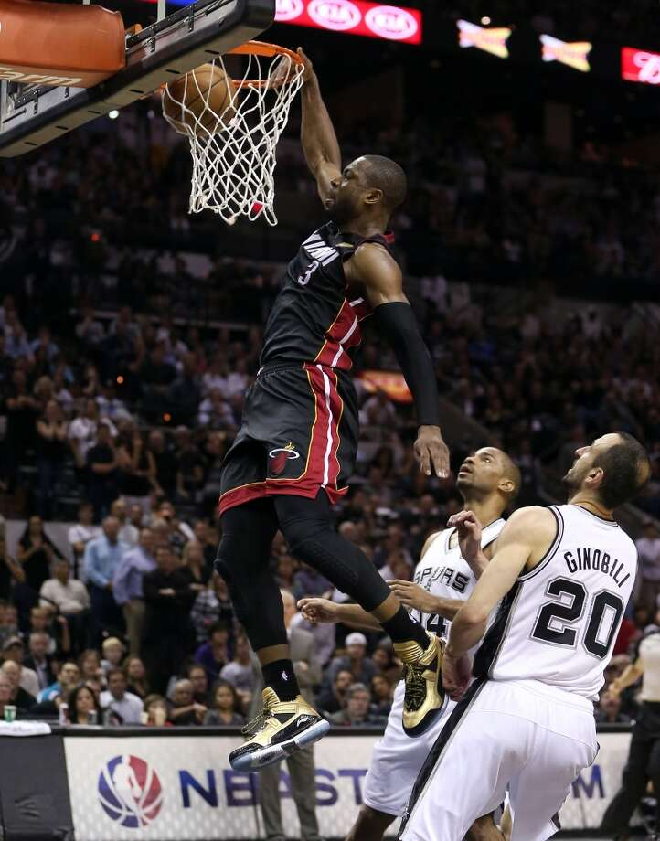 Dwyane Wade dunks the ball in front of Manu Ginobili.