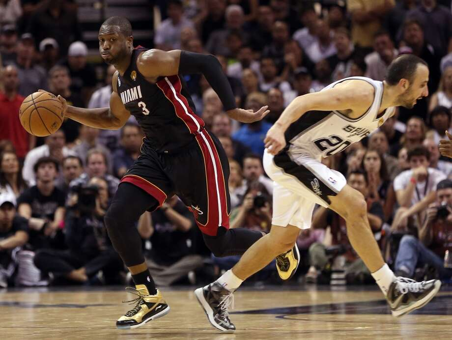 Dwyane Wade with the ball against Manu Ginobili.