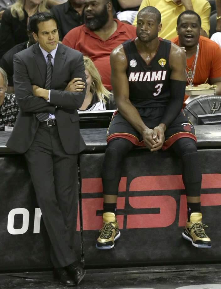 Erik Spoelstra and Dwyane Wade watch from courtside.