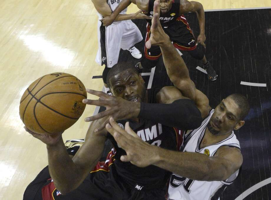Dwyane Wade is defended by Tim Duncan during the first half.