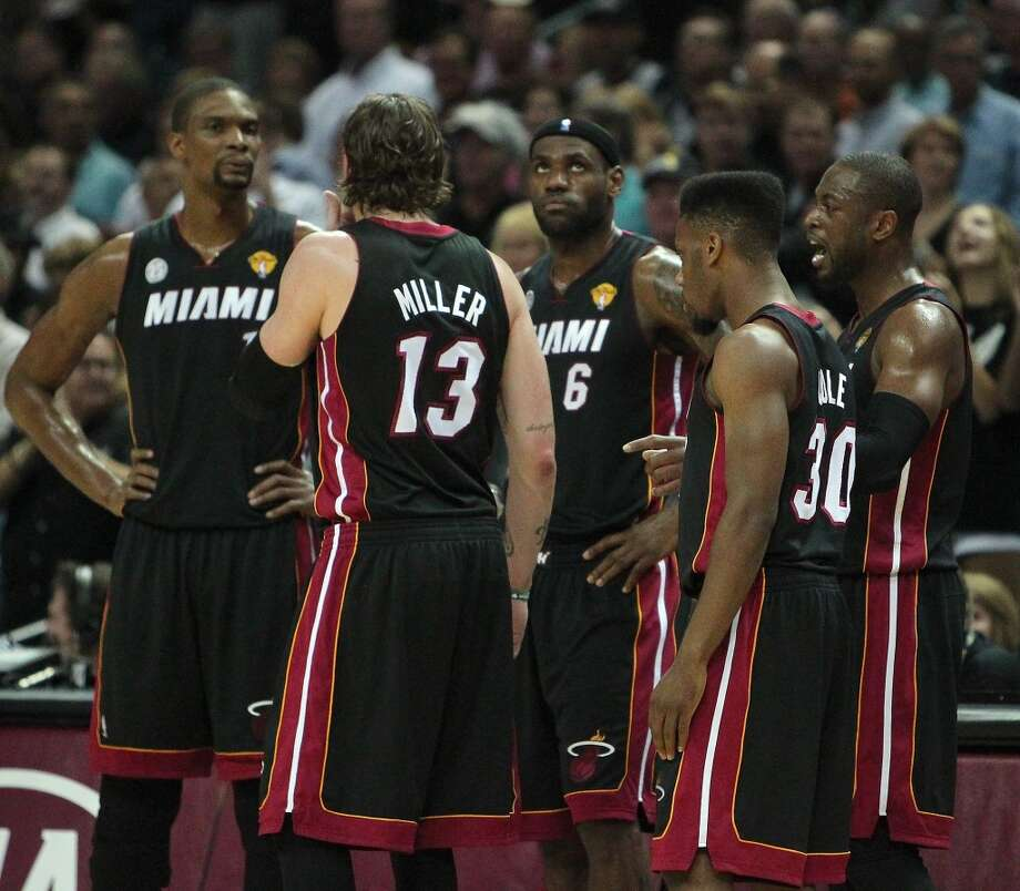 Heat guard Dwyane Wade, right, talks with teammates, from left to right, forward Chris Bosh, forward Mike Miller, forward LeBron James and guard Norris Cole.