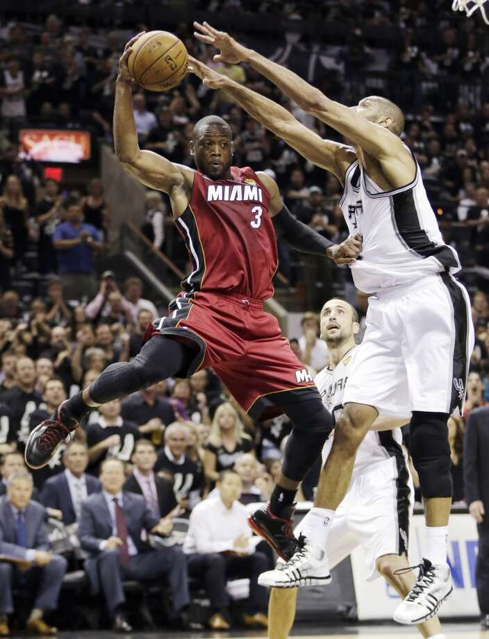 Dwyane Wade (3) is pressured by Tim Duncan (21) during the second half.