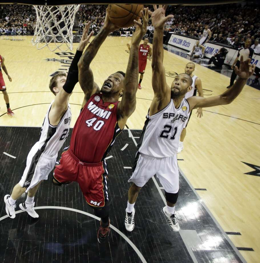 Udonis Haslem (40) goes up for a shot against Tiago Splitter (22), of Brazil, and Tim Duncan (21).