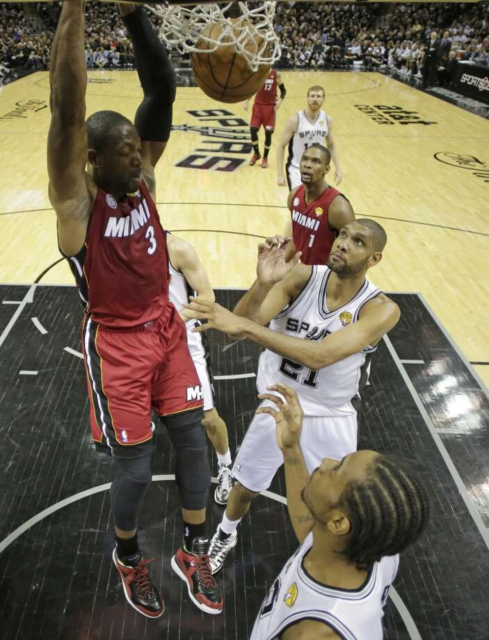 Dwyane Wade (3) dunks as Tim Duncan (21) and Kawhi Leonard react.