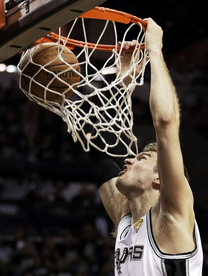 Tiago Splitter, of Brazil, dunks against the Heat.