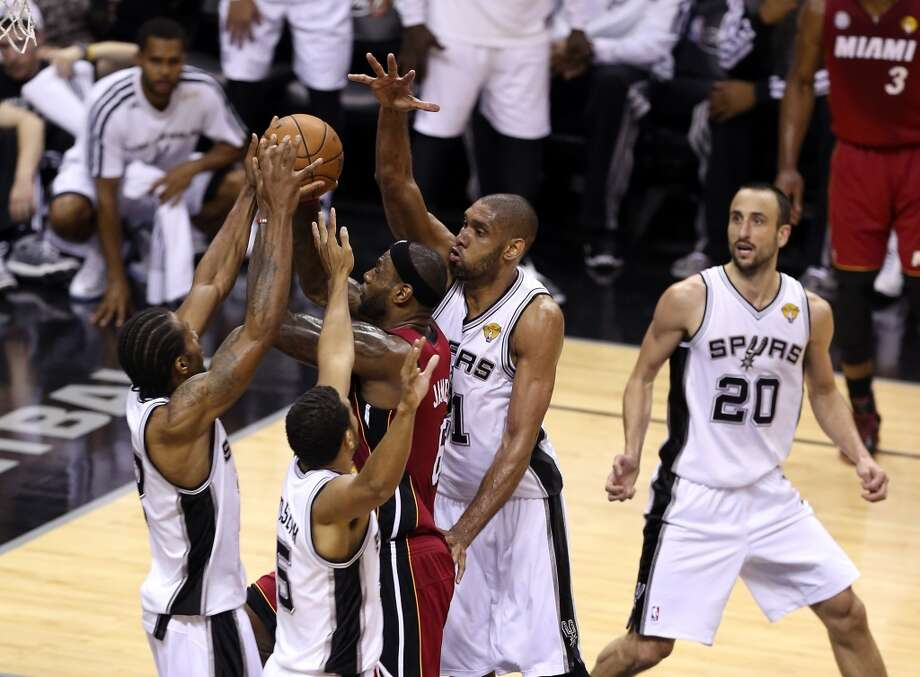 LeBron James #6 of the Heat goes up for a shot against Cory Joseph #5, Kawhi Leonard #2 and Tim Duncan #21 of the Spurs.