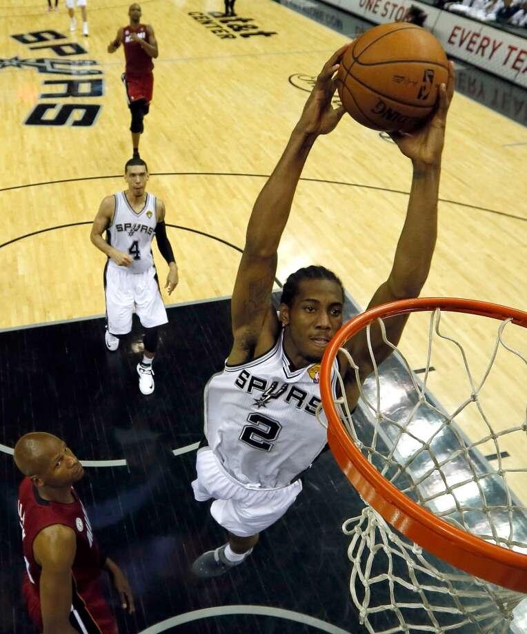 Kawhi Leonard #2 of the Spurs dunks against the Heat.