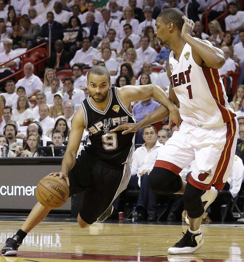 Tony Parker of the Spurs drives against Heat forward Chris Bosh.