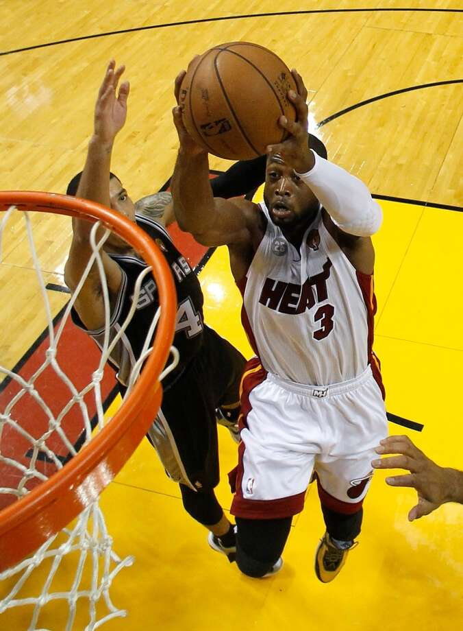 Dwyane Wade of the Heat dunks against the Spurs.