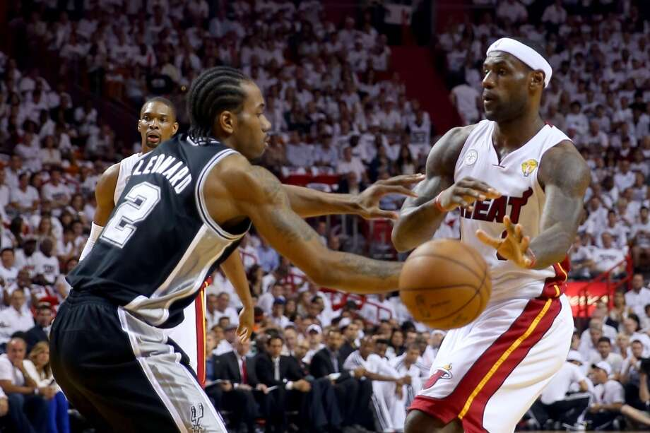LeBron James of the Heat passes the ball as Kawhi Leonard defends.