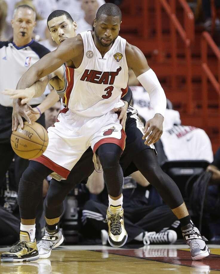 Heat guard Dwyane Wade jockeys for position against Danny Green of the Spurs.