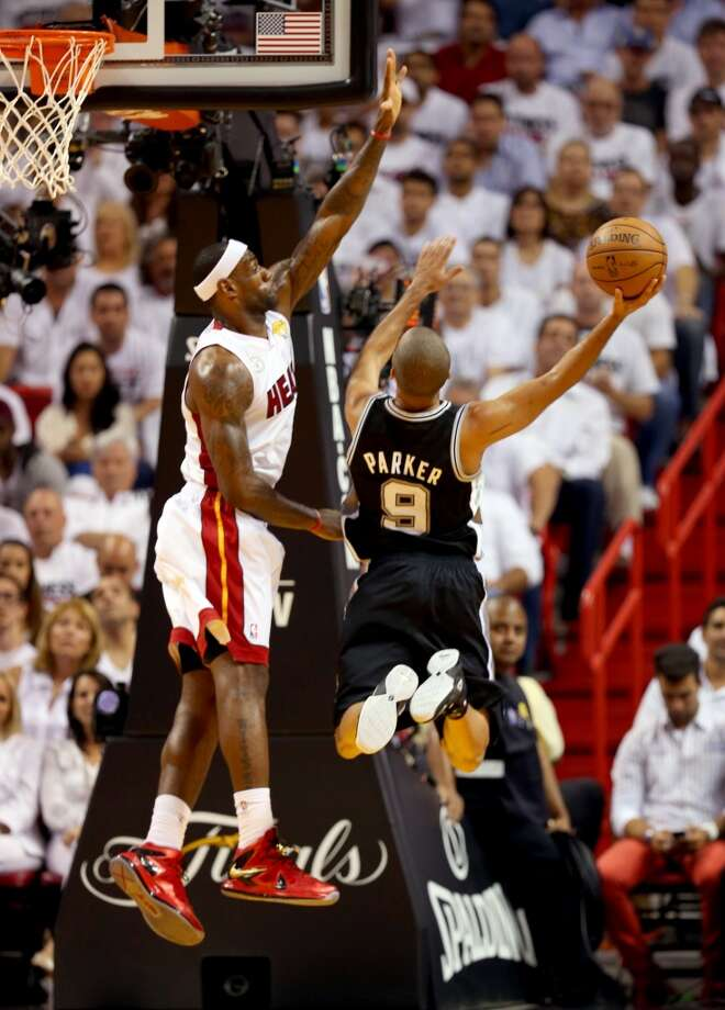 LeBron James of the Heat contests a shot by Spurs point guard Tony Parker.