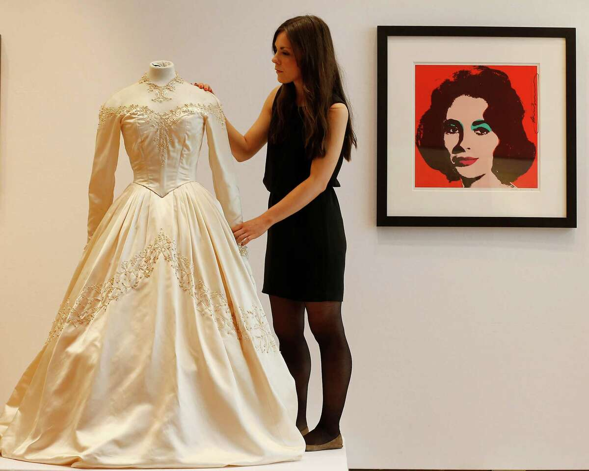 A Christie's employee adjusts Elizabeth Taylor's first wedding dress, designed by the legendary costume designer Helen Rose, at the auction house Christie's in London, Wednesday, June 19, 2013. The wedding dress is part of the auction 120 years of Pop Culture, which is showcasing important memorabilia dating from every decade of the past century of popular culture from the ubiquitous industries of film and music. The estimated price is 30,000 ?- 50,000 pound (46,000-78,000 dollars). (AP Photo/Frank Augstein)
