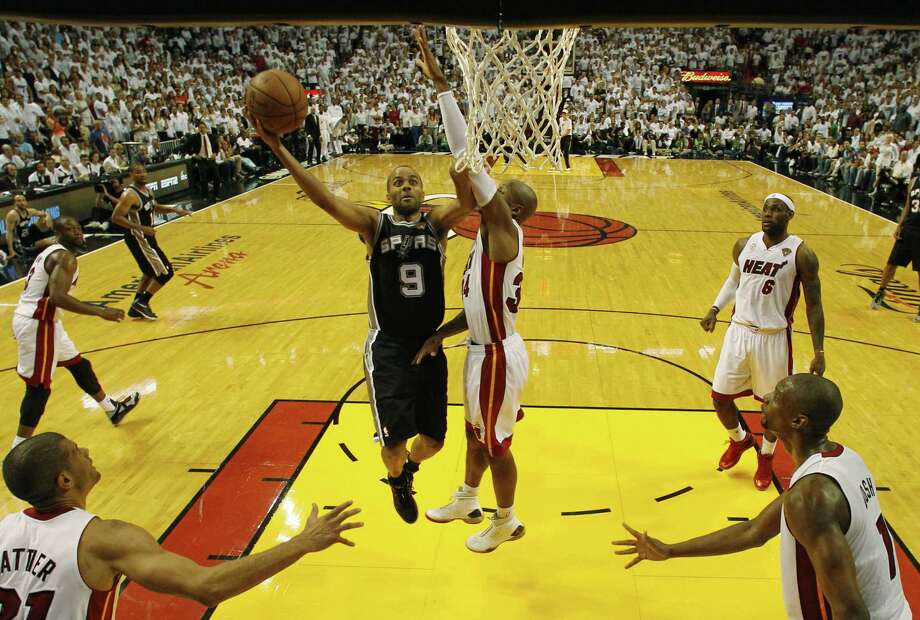 San Antonio Spurs guard Tony Parker (9) drives to the basket as Miami Heat guard Ray Allen (34) defends.