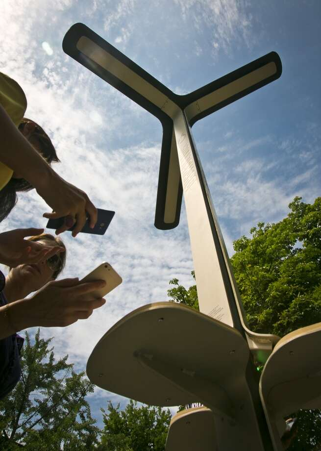 Users check their phones after solar charging the devices on Tuesday, June 18, 2013 in New York.  The city has teamed up with AT&T to install 25 solar powered charging stations for public use, available for free in parks and beaches across the five boroughs over the summer. Photo: Bebeto Matthews, Associated Press