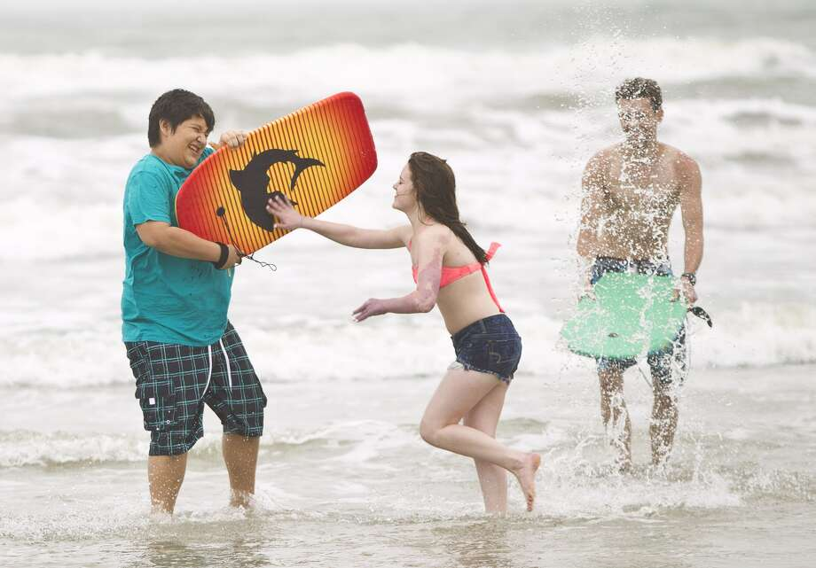 Cameron Heth, center, pushes Justin Perez, left, both of Cypress, after he splashed her as they visit Stewart Beach, April 17, 2013, in Galveston. (Nick de la Torre / Chronicle)