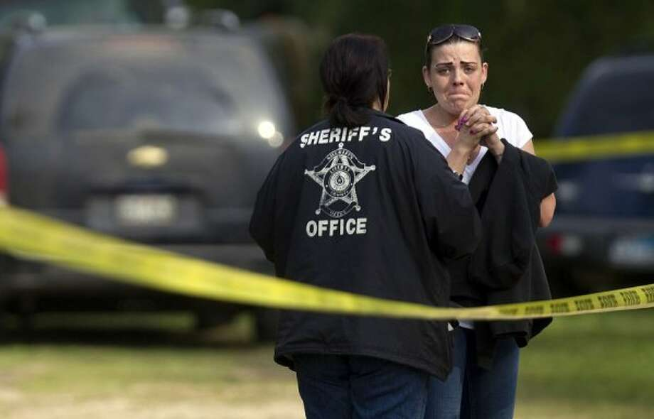 April Davis looks on as local authorities including Houston police divers along with Texas Equusearch search for her son. (Johnny Hanson / Houston Chronicle)