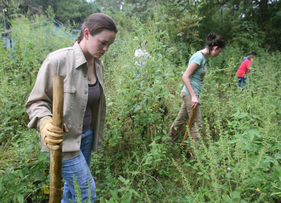 Oct. 6, 2007: Equusearch volunteers walk the thick-wooded areas of Acres Homes to ensure that there are no more homicide victims or evidence before a cleanup effort is launched. Photo: Billy Smith II, Chronicle
