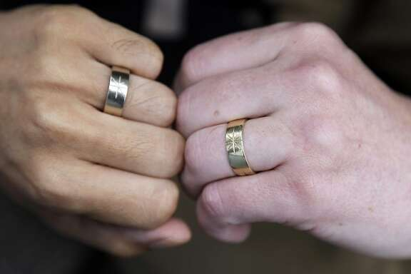 Thom Watson, right, and Jeff Tabaco show the rings which they exchanged during their 2009 wedding ceremony at their home in Daly City, Calif., Monday, June 10, 2013. The U.S. Supreme Court is expected to rule this month in a lawsuit that challenged the constitutionality of the gay marriage ban, known as Proposition 8. (AP Photo/Marcio Jose Sanchez)