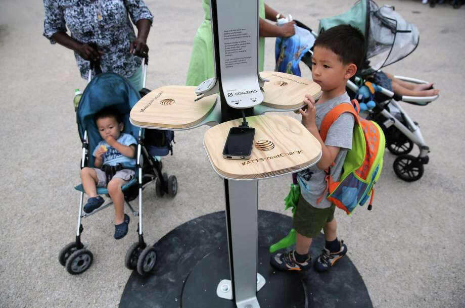 NEW YORK, NY - JUNE 18:  People charge their cell phones at a free solar-powered charging station set up by AT&T at Brooklyn Bridge Park on June 18, 2013 in the Brooklyn borough of New York City. Twenty-five solar-powered charging stations are being set up in parks, beaches and other spaces throughout New York City as part of the AT&T pilot project. The towers can accommodate six devices at a time with dedicated ports for iPhones, BlackBerrys and Androids, regardless of the wireless carrier. Photo: John Moore, Getty Images / 2013 Getty Images