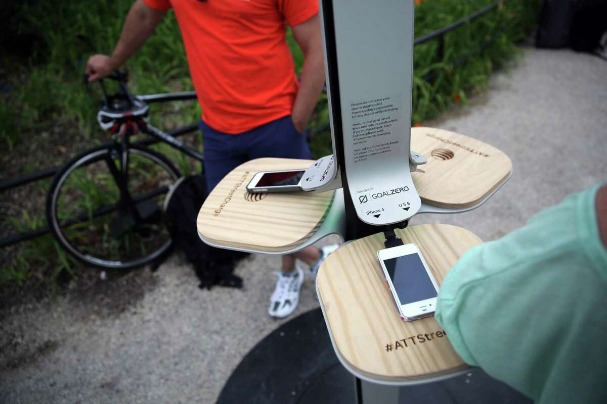 NEW YORK, NY - JUNE 18: People charge their cell phones at a free solar-powered charging station set up by AT&T at Brooklyn Bridge Park on June 18, 2013 in the Brooklyn borough of New York City. Twenty-five solar-powered charging stations are being set up in parks, beaches and other spaces throughout New York City as part of the AT&T pilot project. The towers can accommodate six devices at a time with dedicated ports for iPhones, BlackBerrys and Androids, regardless of the wireless carrier.
