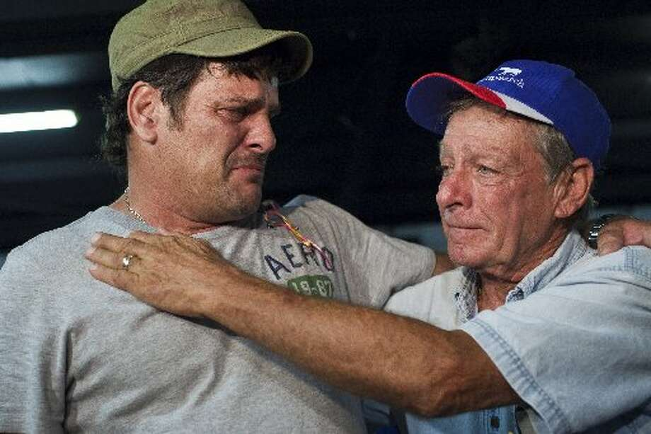 Michael Elkins, father of victim Amber Chantel Elkins, left, embraces Tim Miller, founder and director of Texas EquuSearch, before a July 2011 candlelight vigil, held for Amber, who police believe was murdered by her boyfriend. Photo: Eric Kayne