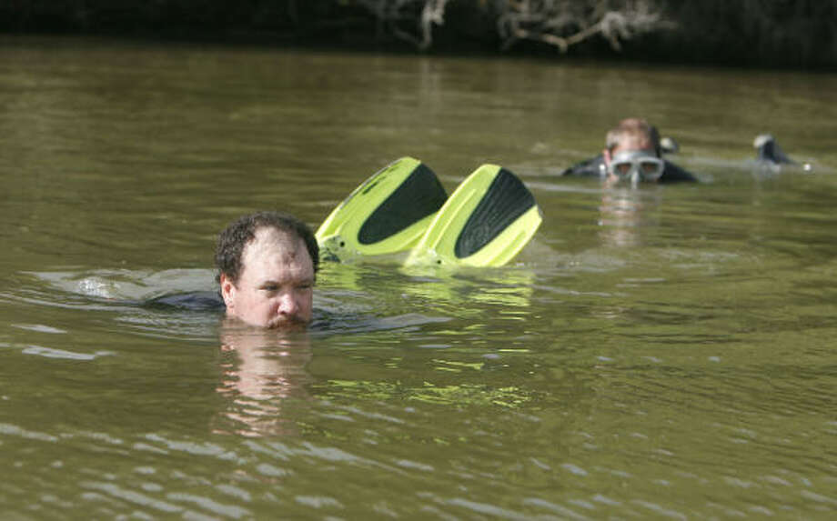 Richard Allen, from left, and David Grindle of Texas Dive and Recovery working along with EquuSearch scan the banks of Whites Lake in Highland on April 14, 2006. Photo: Billy Smith II, CHRONICLE