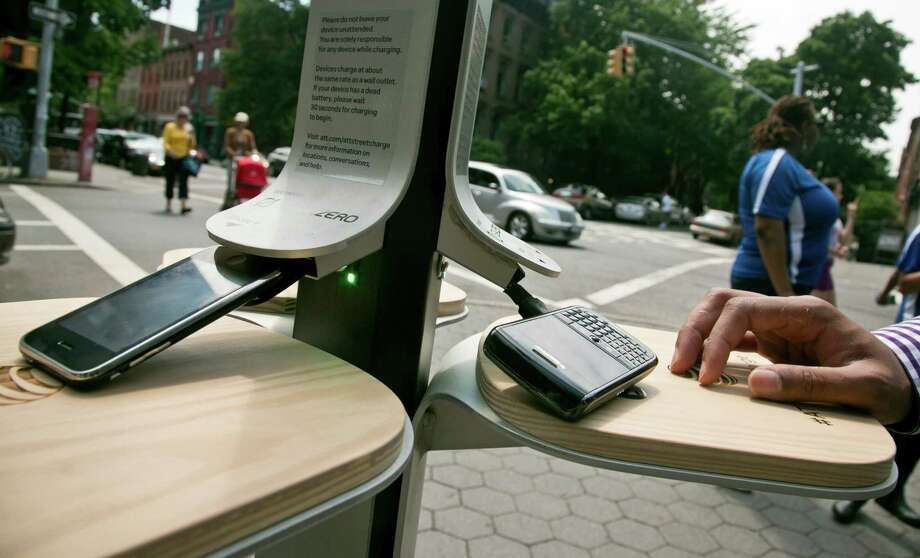 Cellphones powerup with solar energy on Tuesday, June 18, 2013 in New York.  The city has teamed up with AT&T to install 25 solar powered charging stations for public use, available for free in parks and beaches across the five boroughs over the summer. Photo: Bebeto Matthews, AP / AP