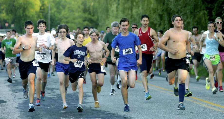 The field of more than 500 runners and walkers kicks off May 31 in the second annual Bank Street Theater Twilight Run 5K road race in New Milford. Among the early challengers are Danbury teens Jack Adamski (432) and Jake Roberts (600), but everyone was soon left in the wake of shirtless Dan DeCrescenzo, an ex-New Milford High cross country and track standout, shown here just to their left. Eventual women's champ Mary Zengo (484), right, of Wilton is among the early frontrunners. Photo: Norm Cummings