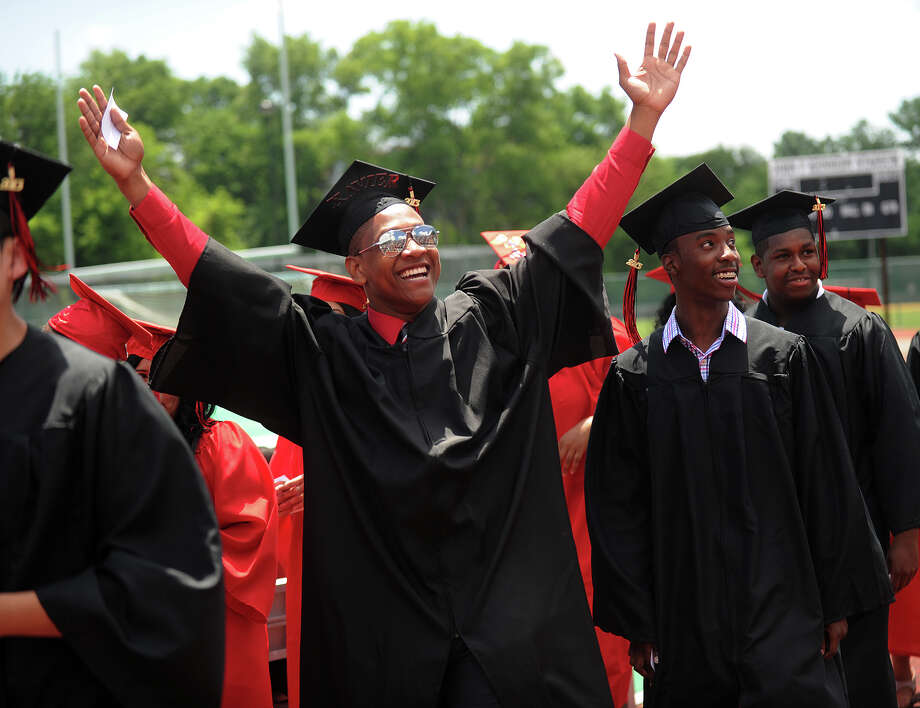 Xavier Hardison gestures to the crowd as he walks in with his fellow graduates to the Central High School graduation at Kennedy Stadium in Bridgeport, Conn. on Wednesday, June 19, 2013. Photo: Brian A. Pounds / Connecticut Post