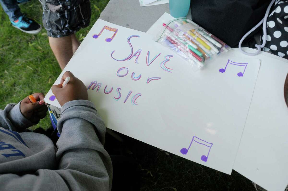 A student makes a sign as members of Albany High School's select choir, jazz band, Albanettes, men's choir and the quartet held a rally in Academy Park on Wednesday, June 19, 2013 in Albany, NY. (Paul Buckowski / Times Union)