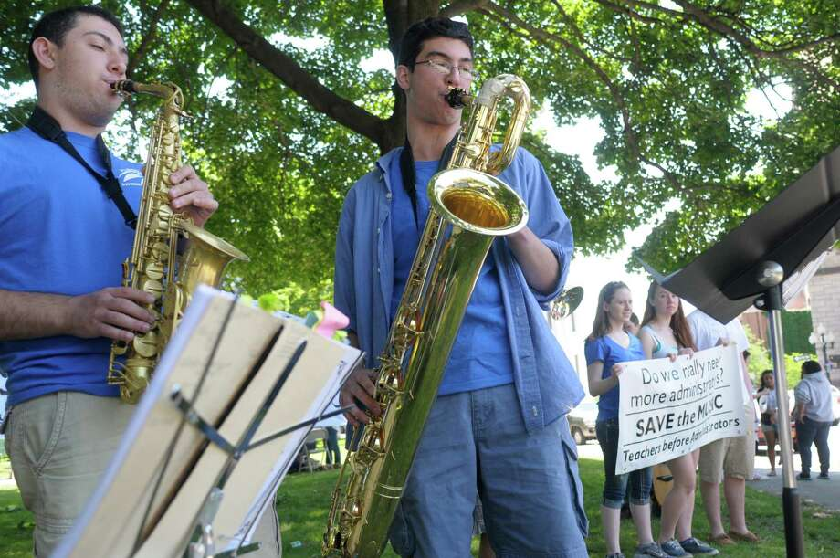 Graduating senior, Justin Dimase, left, and sophomore Livio Fasullo play with other members of the jazz band as members of Albany High School's select choir, jazz band, Albanettes, men's choir and the quartet held a rally in Academy Park on Wednesday, June 19, 2013 in Albany, NY.   (Paul Buckowski / Times Union) Photo: Paul Buckowski