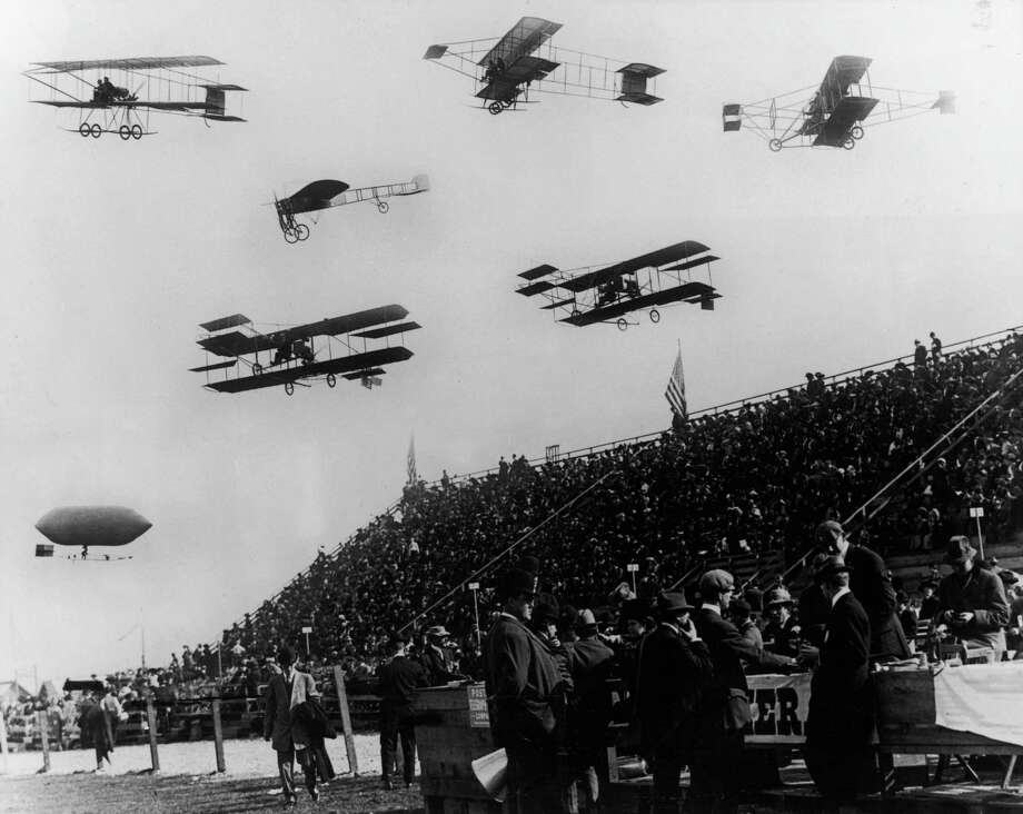 Six airplanes and a dirigible fly over the audience during Reims, France, Aviation Week in August 1909. Photo: American Stock Archive, Getty Images / Archive Photos