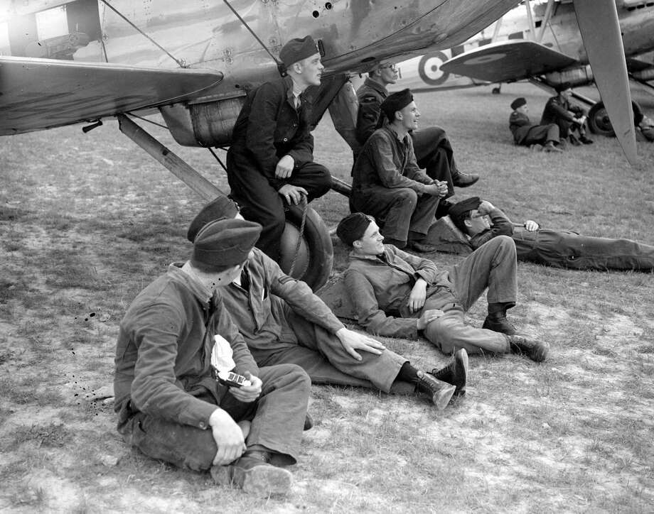 Airmen sit under planes during the Daily Express Gatwick Airshow in 1938. Photo: London Express, Getty Images / Hulton Archive